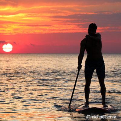 Persona practicando paddleboard con el sol anocheciendo de fondo
